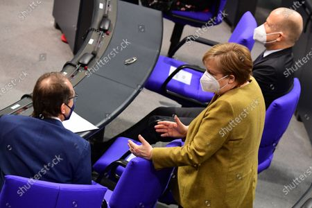German Chancellor Angela Merkel (C) talks to Christian Social Union (CSU) regional group chairman in the German parliament Bundestag Alexander Dobrindt (L) next to Christian Democratic Union (CDU) and Christian Social Union (CSU) faction chairman in the German parliament Bundestag Ralph Brinkhaus (R) during a session at the German parliament Bundestag in Berlin, Germany, 04 March 2021. Members of the German parliament Bundestag discussed the ongoing COVID-19 pandemic situation in the country one day after new lockdown measures and opening scenarios were resolved.