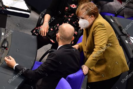 German Chancellor Angela Merkel (R) talks to Christian Democratic Union (CDU) and Christian Social Union (CSU) faction chairman in the German parliament Bundestag Ralph Brinkhaus during a session at the German parliament Bundestag in Berlin, Germany, 04 March 2021. Members of the German parliament Bundestag discussed the ongoing COVID-19 pandemic situation in the country one day after new lockdown measures and opening scenarios were resolved.