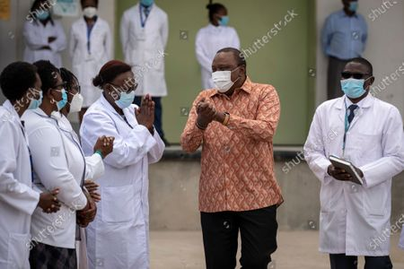 Kenya's President Uhuru Kenyatta, center, gestures during a visit to the central vaccine depot in Kitengela town on the outskirts of Nairobi, in Kenya . Around 1.02 million doses of the AstraZeneca COVID-19 vaccine manufactured by the Serum Institute of India arrived in the country on Wednesday as part of the COVAX facility