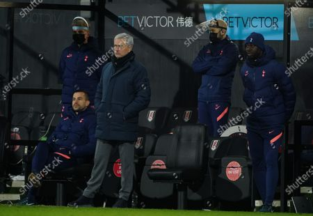 Tottenham manager Jose Mourinho stands in the dugout area near coach Ledley King
