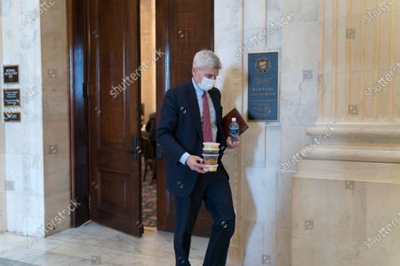 Sen. Bill Cassidy, R-La., carries containers of food as he leaves a Republican policy luncheon on Capitol Hill in Washington, . Senate will be working into the night on the Democrats' $1.9 trillion COVID relief package