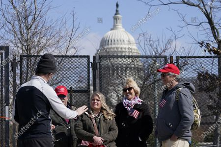 With the U.S. Capitol in the background, from left, District of Columbia resident Alex Howard talks with supporters of former President Donald Trump, John Carson, of California, Karyn Carson, Lois Houser and Matthew Giannini, of Florida, in Washington