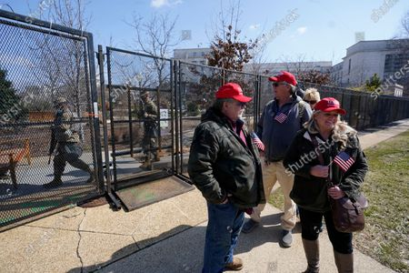 Supporters of former President Donald Trump, John Carson, of California, left, Karyn Carson, right, Lois House and Matthew Giannini, of Florida, second from right, stand outside of security fencing around the U.S. Capitol as members of the national guard walk on the other side, in Washington