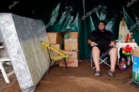 Gabriel Gonzalez, whose mother Maria Torres is being treated for COVID-19 in the ICU of the Ineram Respiratory Hospital, camps out under a tent outside the hospital in Asuncion, Paraguay, . Gonzalez said he's spent more than $10,000 on medicine over 15 days for his mother