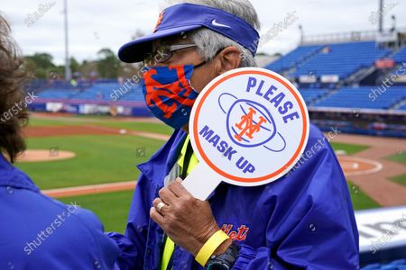 "Stock Picture of Usher Barbara Raymond wears a face mask as she holds a sign asking fans to ""Please Mask Up"" before a spring training baseball game between the New York Mets and the Washington Nationals, in Port St. Lucie, Fla"