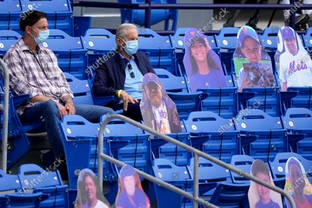 Former owner of the New York Mets Fred Wilpon, right, sits among cardboard cutouts during a spring training baseball game between the New York Mets and Washington Nationals, in Port St. Lucie, Fla