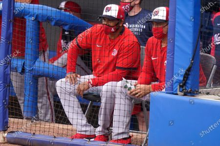 Washington Nationals manager Dave Martinez, left, watches a spring training baseball game against the New York Mets, in Port St. Lucie, Fla