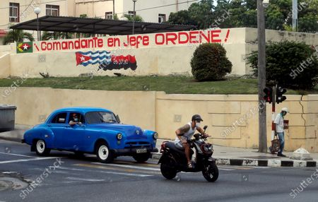 A man on a motorcycle and a classic car walk alongside a graffiti with revolutionary slogans in Havana, Cuba, 04 March 2021. The Communist Party of Cuba (PCC) elects this 04 March the delegates to its VIII Congress, in which it is expected that Raul Castro will retire from politics and hand over the leadership of the all-powerful formation to the president of the country, Miguel Diaz-Canel.