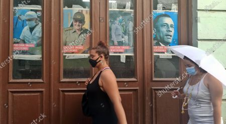 Two women pass by several posters with revolutionary slogans in Havana, Cuba, 04 March 2021. The Communist Party of Cuba (PCC) elects this 04 March the delegates to its VIII Congress, in which it is expected that Raul Castro will retire from politics and hand over the leadership of the all-powerful formation to the president of the country, Miguel Diaz-Canel.