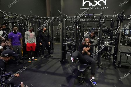 House of Athlete Scouting Combine founder and former NFL player Brandon Marshall, right foreground, is congratulated by Isaiah Ross after Marshall completed a series of bench presses for the combine participants on the second day of the House of Athlete Scouting Combine, in Weston, Fla