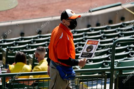 An usher at Ed Smith Stadium holds a sign reminding fans to wear face covering as patrols the stand during a spring training baseball game between Baltimore Orioles and Boston Red Sox, in Sarasota, Fla