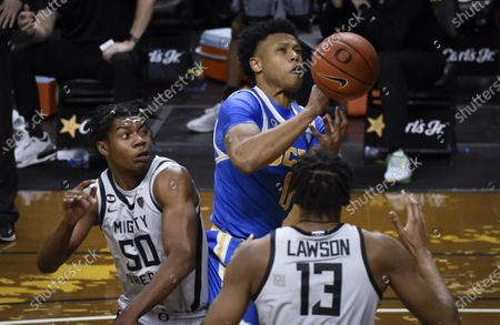 Guard Jaylen Clark (0) tries to haul in a rebound over Oregon forward Eric Williams Jr. (50) and Oregon forward Eugene Omoruyi (2) during the first half of an NCAA college basketball game Wedesday, in Eugene, Ore