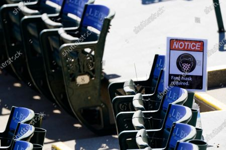 Sign resting on a row of unused seats at Ed Smith Stadium reminds fans to wear a mask during a spring training baseball game between Boston Red Sox and Baltimore Orioles, in Sarasota, Fla