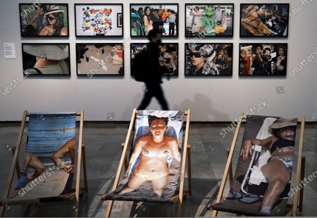 Stock Picture of A visitor passes in front of artworks by British photographer Martin Parr on display during the exhibition 'Parrathon' at the Centre of Carme in Valencia, Spain, 03 March 2021. The exhibition features photographs from the Magnum Photos agency with which Parr works since 1994.