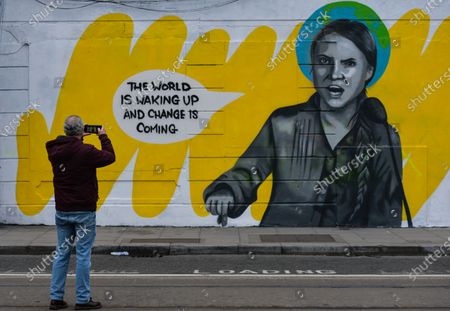 Stock Image of A man takes a photo of Dublin mural of Greta Thunberg repaired after being vandalised. A new mural by Irish artist Emmalene Blake, representing Greta Thunberg, a Swedish environmental activist, was vandalised with the words 'SLUT X George Soros' - just one day after its completion.On Thursday, 4 March, 2021, in Dublin, Ireland.