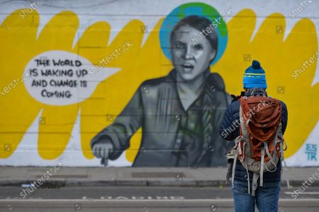Stock Picture of A man takes a photo of Dublin mural of Greta Thunberg repaired after being vandalised. A new mural by Irish artist Emmalene Blake, representing Greta Thunberg, a Swedish environmental activist, was vandalised with the words 'SLUT X George Soros' - just one day after its completion.On Thursday, 4 March, 2021, in Dublin, Ireland.