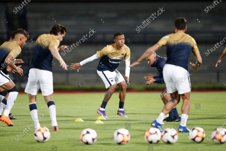 Pumas' Gabriel Torres, center, warms up prior to a Mexican soccer league match against Santos at University Olympic Stadium in Mexico City