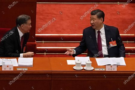 Chinese President Xi Jinping, right, chats with Wang Yang, chairman of the Chinese People's Political Consultative Conference (CPPCC) during the opening session of China's National People's Congress (NPC) at the Great Hall of the People in Beijing, . Premier Li Keqiang has set a healthy economic growth target and vowed to make this nation self-reliant in technology amid tension with Washington and Europe over trade and human rights