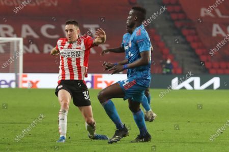 (L-R) Ryan Thomas #30 of PSV, Ousseynou Ba #24 of Olympiakos  during the UEFA Europa League match between PSV v Olympiakos Piraeus at the Philips Stadium on February 25, 2021 in Eindhoven Netherlands.
