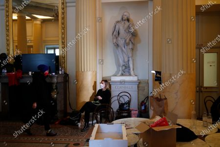 Out-of-work French culture and tourism workers sit inside the iconic Odeon theater, in Paris. Out-of-work French culture and tourism workers have occupied the theater on Paris' Left Bank to demand more government support after a year of pandemic that has devastated their livelihoods. At center is a statue of French 17th century tragedian Pierre Corneille