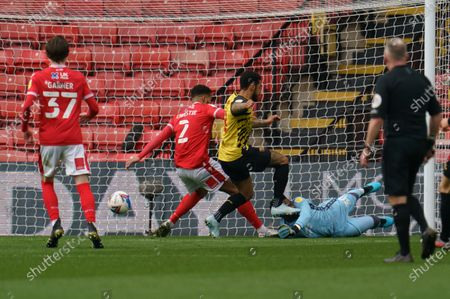 Before the goal by \w11, Nottingham Forest Goalkeeper Brice Samba (30) is kicked by Andre Gray of Watford (18) when diving for the loose ball