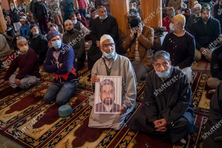 An elderly Kashmiri man holds a photograph of Kashmiri separatist leader Mirwaiz Umar Farooq, as a mark of protest inside Jamia Masjid in Srinagar, Indian controlled Kashmir, . Indian government forces fired pellets outside the mosque to disperse Kashmiri protesters during a protest against the continuous detention of Farooq, who is under house detention since August 2019, when India scrapped the region's semi-autonomous status