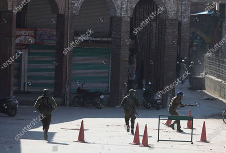 Policemen chase protestors during clashes outside the Jamia Masjid following Friday prayers in Srinagar, India, 05 March 2021. Clashes erupted between demonstrators and policemen during a protest against the detention of separatist leader and Kashmir's Chief cleric Mirwaiz Umar Farooq, under house arrest since August 2019.