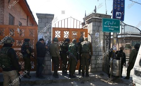 Police watch as protestors gather outside the Jamia Masjid following Friday prayers in Srinagar, India, 05 March 2021. Clashes erupted between demonstrators and policemen during a protest against the detention of separatist leader and Kashmir's Chief cleric Mirwaiz Umar Farooq, under house arrest since August 2019.