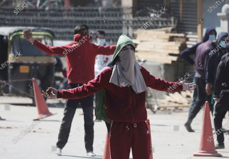 Stock Photo of Protestors react during clashes with police outside the Jamia Masjid following Friday prayers in Srinagar, India, 05 March 2021. Clashes erupted between demonstrators and policemen during a protest against the detention of separatist leader and Kashmir's Chief cleric Mirwaiz Umar Farooq, under house arrest since August 2019.