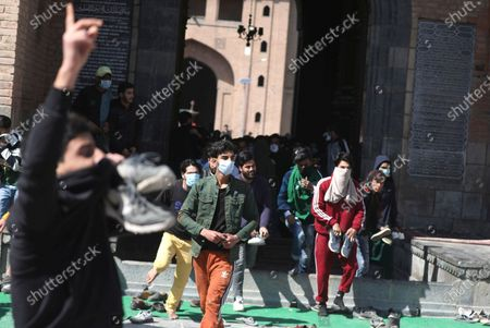 Protestors react during clashes with police outside the Jamia Masjid following Friday prayers in Srinagar, India, 05 March 2021. Clashes erupted between demonstrators and policemen during a protest against the detention of separatist leader and Kashmir's Chief cleric Mirwaiz Umar Farooq, under house arrest since August 2019.