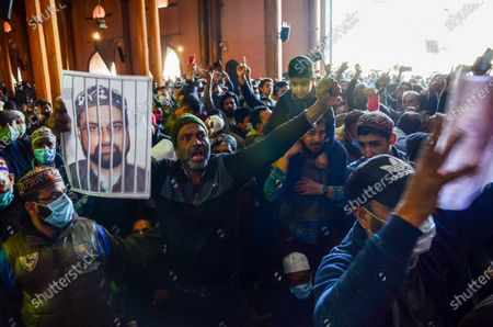 A Kashmiri protester gestures while holding a portrait of Hurriyat chairman and Valleyís chief cleric Mirwaiz Umar Farooq, during the demonstration.Protesters demonstrate against the continuous detention of Kashmiri separatist leader and Chief Cleric Mirwaiz Umar Farooq, who is under house detention since August 2019, when India scrapped the region's semi-autonomous status.