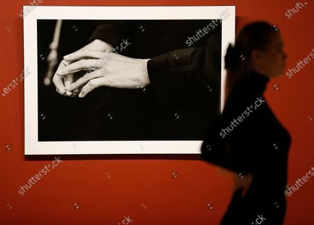 A visitor walks past a picture depicting the hands of British actress Kate Winslet by Germany photographer Peter Lindbergh during the exhibition '2017. Pirelli Calendar by Peter Lindbergh and More' at the modern art museum Erarta in St. Petersburg, Russia, 05 March 2021.