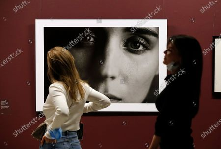 Visitors look at a picture of US actress Rooney Mara by Germany photographer Peter Lindbergh during the exhibition '2017. Pirelli Calendar by Peter Lindbergh and More' at the modern art museum Erarta in St. Petersburg, Russia, 05 March 2021.