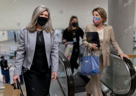 Sen. Joni Ernst, R-Iowa, left, and Sen. Shelley Moore Capito, R-W.Va., head to the chamber as the Senate holds a voting marathon on the Democrats' $1.9 trillion COVID-19 relief bill that's expected to end with the chamber's approval of the measure, at the Capitol in Washington