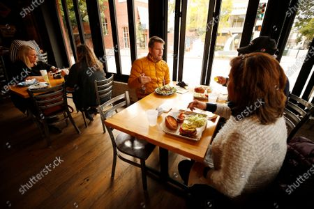 """Christine Wallace, left, with Melissa Ellsworth dine at one table as Chris Allen, Hamid Keshtgar and Shahin Aminilari, right, dine at another with fewer tables inside Mo's Smokehouse BBQ in downtown San Luis Obispo as San Luis Obispo county moved into the red tier that allows for indoor dining and gym reopening. Mo's Smokehouse BBQ general manager Nancy Snyder said, """"We were ready and excited to open."""" downtown on Wednesday, March 3, 2021 in San Luis Obispo, CA. (Al Seib / Los Angeles Times)."""