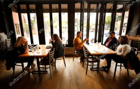 """Stock Photo of Christine Wallace, left, with Melissa Ellsworth dine at one table as Chris Allen, Hamid Keshtgar and Shahin Aminilari, right, dine at another with fewer tables inside Mo's Smokehouse BBQ in downtown San Luis Obispo as San Luis Obispo county moved into the red tier that allows for indoor dining and gym reopening. Mo's Smokehouse BBQ general manager Nancy Snyder said, """"We were ready and excited to open."""" downtown on Wednesday, March 3, 2021 in San Luis Obispo, CA. (Al Seib / Los Angeles Times)."""