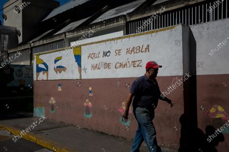 A man walks past a mural depicting the eyes of the late Venezuelan President Hugo Chavez in Caracas, Venezuela, 04 February 2021 (issued 05 March 2021). The writing reads: 'Here we do not speak badly of Chavez.' Chavez died on 05 March 2013 after 14 years in power.