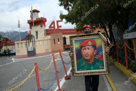 Man holds a painting of late President Hugo Chavez as he waits to enter the Historic Military Museum to visit Chavez's tomb on the eighth anniversary of his death in Caracas, Venezuela, . Chavez continues to unleash mixed feelings among Venezuelans: some remember him as the father of a revolution that defended the poor, while others blame him for the deep and prolonged crisis that overwhelms the South American country