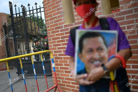 Soldiers guard the Historic Military Museum where a person holds a photo of late President Hugo Chavez, waiting to enter and visit Chavez's tomb on the eighth anniversary of his death in Caracas, Venezuela, . Chavez continues to unleash mixed feelings among Venezuelans: some remember him as the father of a revolution that defended the poor, while others blame him for the deep and prolonged crisis that overwhelms the South American country