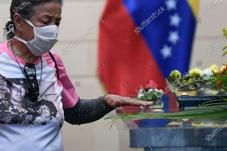 Woman wearing a mask amid the COVID-19 pandemic touches the tomb of late President Hugo Chavez on the eighth anniversary of his death at the Historic Military Museum in Caracas, Venezuela, . Chavez continues to unleash mixed feelings among Venezuelans: some remember him as the father of a revolution that defended the poor, while others blame him for the deep and prolonged crisis that overwhelms the South American country