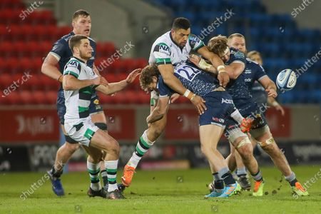 Luther Burrell of Newcastle offloads as he is tackled by Robert and Dan Du Preez of Sale during the Gallagher Premiership Rugby match between Sale Sharks and Newcastle Falcons at the AJ Bell Stadium, Eccles