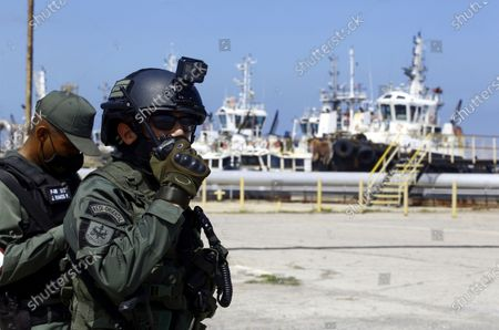 Stock Photo of Soldier gives instructions via a radio on the Guaragua oil dock, during a military drill to mark the eighth death anniversary of President Hugo Chavez, in Puerto Cabello, Venezuela