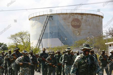Stock Picture of Soldiers patrol near an oil refinery during a military drill to mark the eighth death anniversary of President Hugo Chavez, in Puerto La Cruz, Venezuela