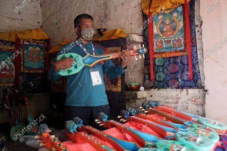 Stock Picture of Tsering Angchok, plays a traditional instrument Dram-nyan (lute) of Changthang (Leh) at the second edition of Enchanting Ladakh, the annual art and craft fair organised by the Union territory's Department of Industries and Commerce at Dilli Haat.
