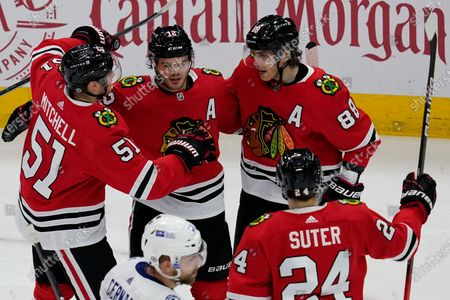 Chicago Blackhawks' Alex DeBrincat, second from left, celebrates with Ian Mitchell, left, Patrick Kane, right, and Pius Suter after scoring his second goal during the second period of an NHL hockey game against the Tampa Bay Lightning in Chicago