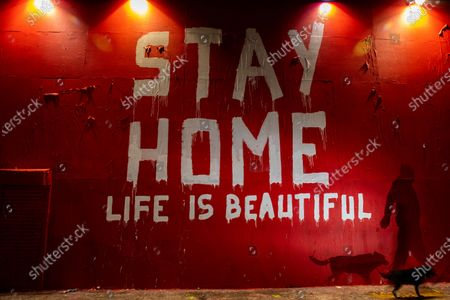 """A man walks by a mural on La Brea Ave by artist Thierry Guetta, aka Mr. Brainwash, has the bold message of """"Stay Home, Life is Beautiful,"""" made during the coronavirus pandemic, photographed Saturday, April 18, 2020, in Los Angeles, CA. Guetta is known for """"Life is Beautiful"""" being used in his pop-art, including in a 2019 campaign for the city of Beverly Hills. (Jay L. Clendenin / Los Angeles Times)"""