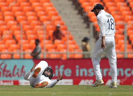 India's Shubman Gill, left, falls on the ground after a shot played by England's Dom Sibley during the third day of fourth cricket test match between India and England at Narendra Modi Stadium in Ahmedabad, India