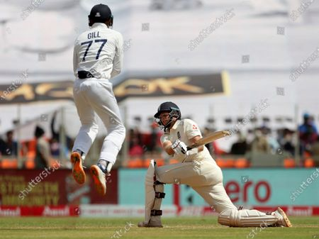 India's Shubman Gill, left, reacts as England's captain Joe Root plays a shot during the third day of fourth cricket test match between India and England at Narendra Modi Stadium in Ahmedabad, India