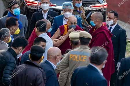 An attendant monk adjusts the face mask on Tibetan spiritual leader the Dalai Lama as he arrives at the Zonal Hospital to receive a COVID-19 vaccine in Dharmsala, India, . Medical officers confirmed that the Tibetan leader got the Covishield vaccine and is not showing any adverse reaction to the vaccine