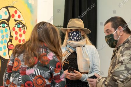Artist Tatiana Lisovskaya discusses her work with attendees. One Art Space in Tribeca held an opening reception for their 5th Annual International Women's Day Art Fair. The exhibition features a diverse, international collection of talent, female-identifying artists of varying ages.